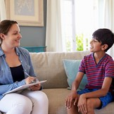 An adopted child talks to an adoption-competent therapist.