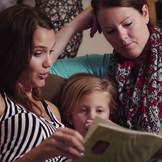 A birth mother, an adoptive mother and an adopted child share a moment in an open adoption.